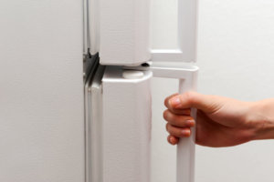 Hand opening refrigerator on white background. Color image in horizontal orientation